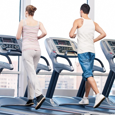 Young woman and man at the gym exercising. Run on a machine. Stock Photo - 15680689