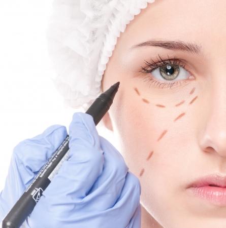 levantar peso: Esteticista toque y dibujar l�neas de correcci�n en la cara de la mujer. Antes operetion cirug�a pl�stica. Aislados en blanco Foto de archivo
