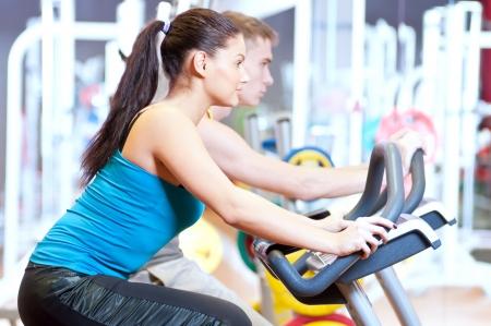 Grupo de dos personas en el gimnasio, el ejercicio de sus piernas haciendo cardio entrenamiento de ciclismo