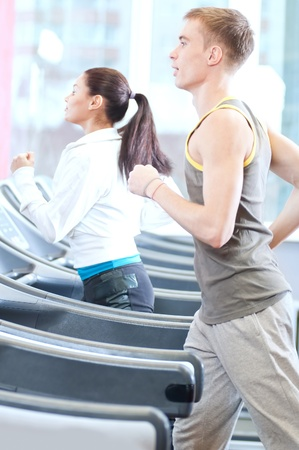 Young woman and man at the gym exercising. Run on a machine. Stock Photo - 15718490