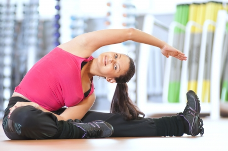 Young fitness woman doing stretching exercises on the floor at the sport gym club photo
