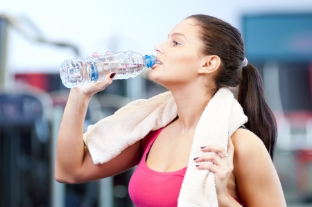 Young oman drinking water after sports. Fitness gym.  photo