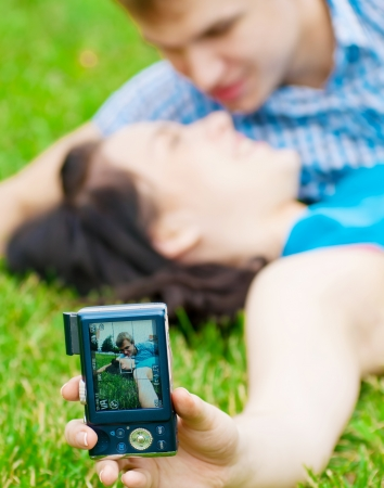 Young emotional happy teenage couple taking picture on grass in city park photo