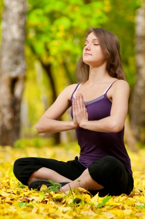 Young woman doing yoga exercises in the autumn city park. Fall photo