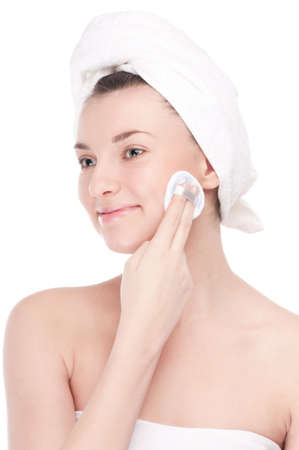 Close-up portrait of young woman with perfect health skin of face and bath towel on head. Isolated on white photo
