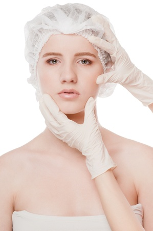 DERMATOLOGY: Medical examination face of beautiful woman by hands in glove - close-up portrait isolated on white  Stock Photo
