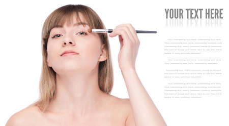 Close-up portrait of young beautiful woman with brush for make-up. Eye shadow zone photo