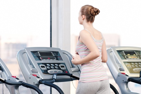 Young woman at the gym exercising. Run on a machine photo
