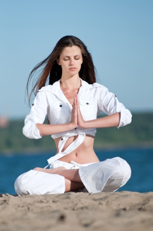 Young beautiful woman practicing yoga on the beach Stock Photo - 16405196