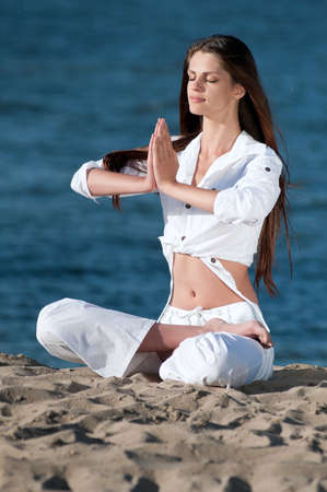 Young beautiful woman practicing yoga on the beach Stock Photo - 16405183