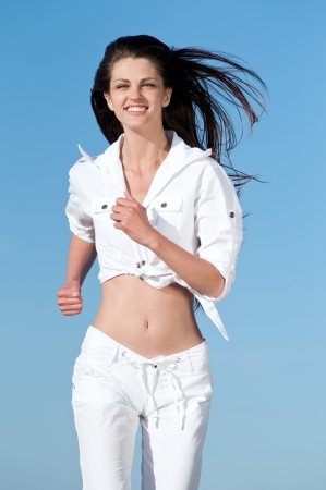Beautiful young sport woman running in sea coast on sunny summer day  Stock Photo - 16405188