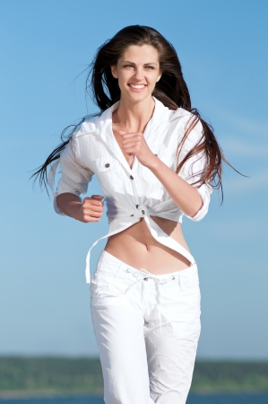 Beautiful young sport woman running in sea coast on sunny summer day Stock Photo - 16405178