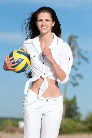 Young beautiful woman playing volleyball on beach. Run with ball Stock Photo - 16405179