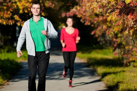 Young fitness couple of man and woman run in park  photo