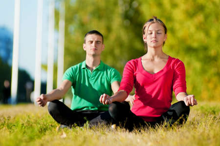Young man and woman woman doing yoga in the sunny summer park Stock Photo - 16405189