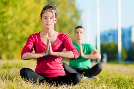 Young man and woman woman doing yoga in the sunny summer park Stock Photo - 16405169