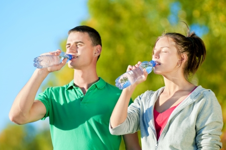 standing water: Man and woman drinking water from bottle after fitness sport exercise