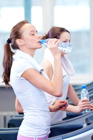 Two young women drinking water after sports. Fitness gym. Stock Photo - 16405194
