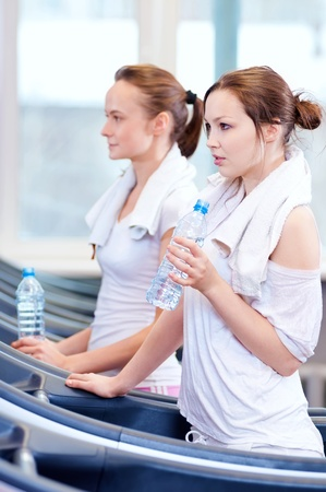 Two young women drinking water after sports. Fitness gym. Stock Photo - 16405187