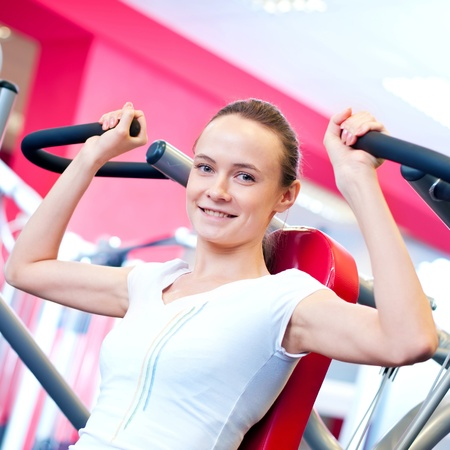 Woman doing fitness training on a butterfly machine with weights in a gym  Stock Photo - 16405192