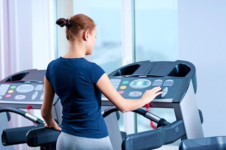 Young woman at the gym exerce. Jog on machine Stock Photo - 16405142