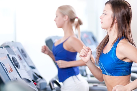 Two young sporty women run on machine in the gym centre Stock Photo - 16405144