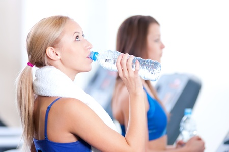 Two young women drinking water after sports. Fitness gym. Stock Photo - 16405175