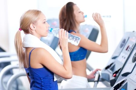Two young women drinking water after sports. Fitness gym. Stock Photo - 16405141