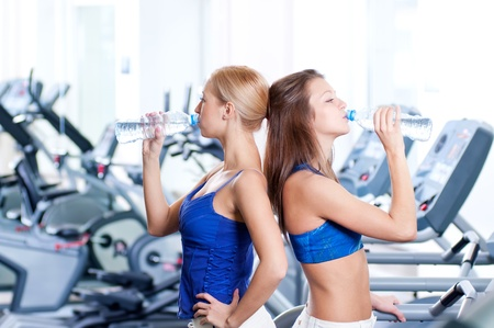 Two young women drinking water after sports. Fitness gym. Stock Photo - 16405153