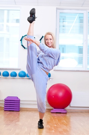Smiling woman do stretching exercise in sports club. Fitness gym Stock Photo - 16405143