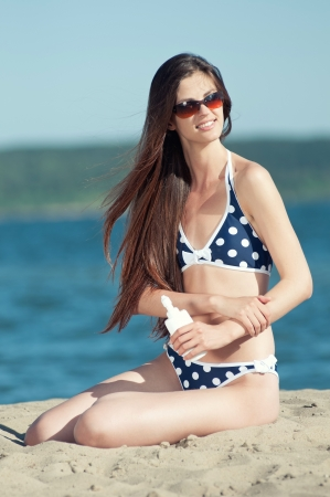 Portrait of woman taking skincare with sunscreen lotion at beach Stock Photo - 16763712