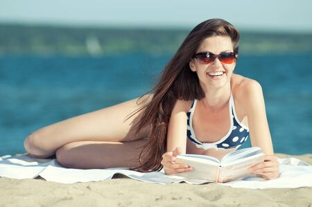 Close up of a beautiful young woman reading book on beach Stock Photo - 16763721