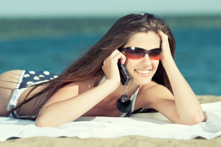 Young smiling woman talking by phone on a beach Stock Photo - 16763738