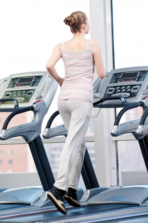Young woman at the gym exercising. Run on a machine Stock Photo - 16763739