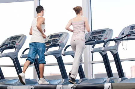 Young woman and man at the gym exercising. Run on a machine.  Stock Photo - 16763716