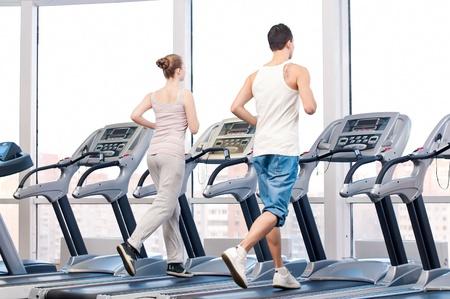 Jonge vrouw en man in de sportschool te oefenen. Draaien op een machine.
