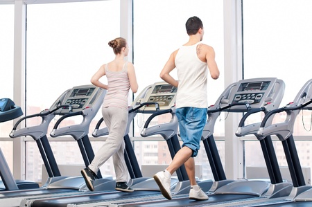 leisure centre: Young woman and man at the gym exercising. Run on a machine.