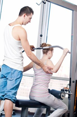 Gym man and woman doing exercise at the fitness club. Personal trainer. Stock Photo - 16763743