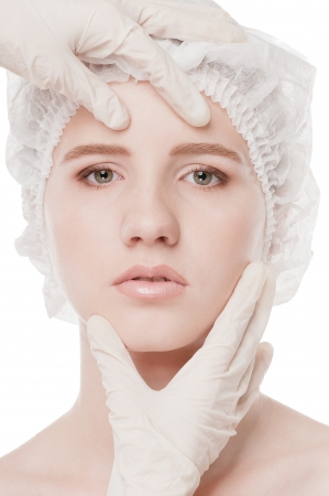 Medical examination face of beautiful woman by hands in glove - close-up portrait isolated on white Stock Photo - 16763768