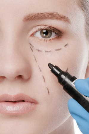 Beautician touch and draw correction lines on woman face. Before plastic surgery operetion. Isolated on white Stock Photo - 16763770