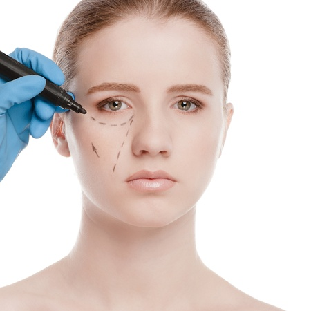 Beautician touch and draw correction lines on woman face. Before plastic surgery operetion. Isolated on white Stock Photo - 16763737
