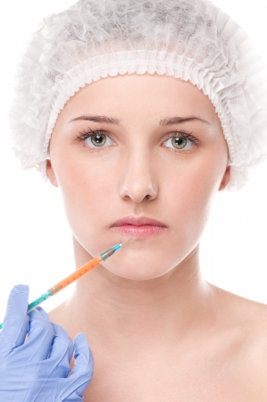 Cosmetic botox injection in the female face. Lips zone. Isolated on white Stock Photo - 16763766