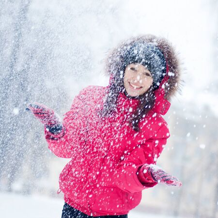 Happy young woman plays with a snow outdoor. Winter day Stock Photo - 16763749