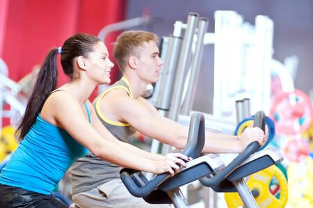 Group of two people in the gym, exercising their legs doing cardio cycling training  Stock Photo - 16763715