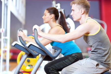 Group of two people in the gym, exercising their legs doing cardio cycling training Stock Photo - 16763736