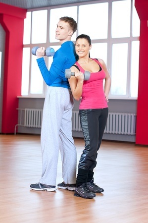 Young man and woman at the fitness gym is doing stretching exercises Stock Photo - 16763731