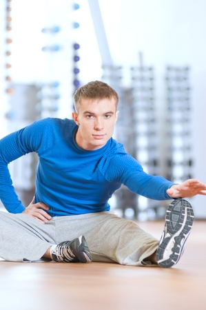 Young fitness man doing stretching exercises on the floor at the sport gym club Stock Photo - 16763751