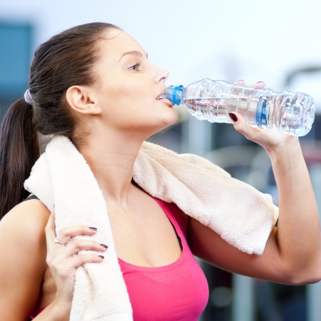 Young oman drinking water after sports. Fitness gym. Stock Photo - 16763741