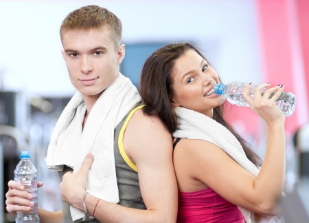 Man and woman drinking water after sport exercises. Fitness gym. Stock Photo - 16763718