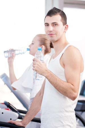 Man and woman drinking water after sports. Fitness gym. Stock Photo - 18207923